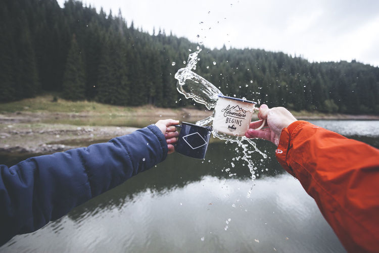 Human hands cheers cold water with splash out of mug isolated on lake and forrest background..Travel concept adventure begins, Lake Bolboci, Romania Refreshment Splashing Water The Creative - 2018 EyeEm Awards Cold Temperature Day Hand Holding Human Hand Leisure Activity Lifestyles Men Mug Mug Shot Nature Non-urban Scene Outdoors People Plant Real People Snow Splashing Tree Two People Warm Clothing Winter EyeEmNewHere A New Perspective On Life