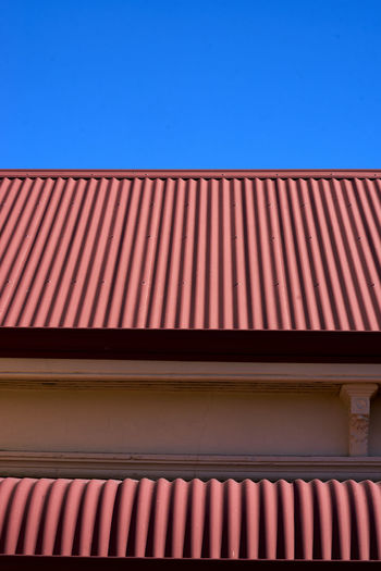 Architecture Awning Blue Building Exterior Built Structure Clear Sky Corrugated Iron Day Low Angle View No People Outdoors Pattern Red Roof