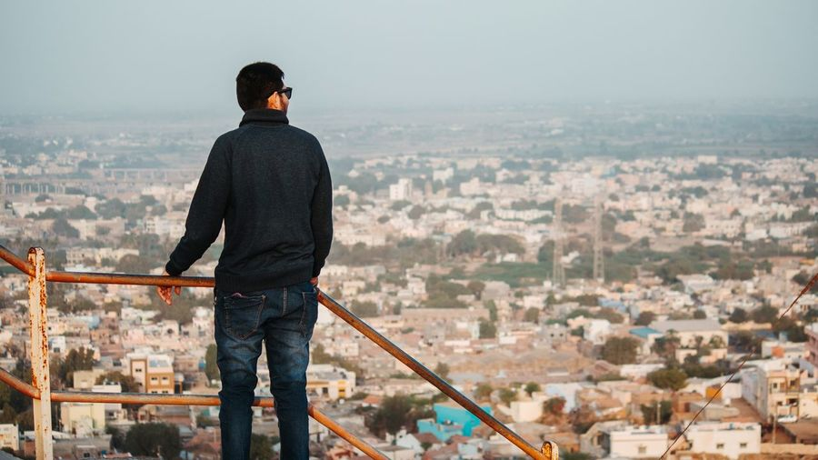 Rear view of man looking at cityscape while standing by railing against sky