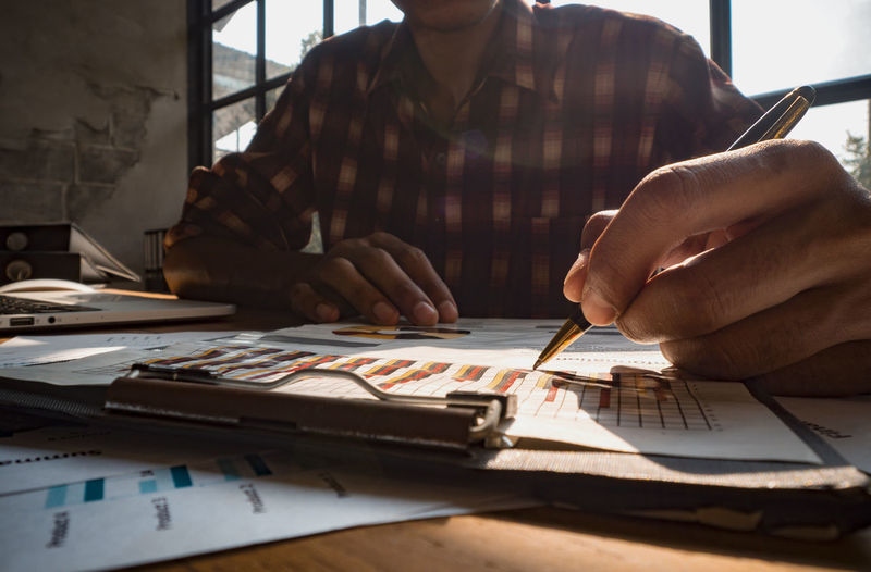 The image of a business designer is holding a pen to write a successful investment income graph. Real People Table One Person Men Indoors  Working Occupation Business Human Hand Adult Holding Paper Day Furniture Front View Midsection Sitting Office Desk Hand Paperwork