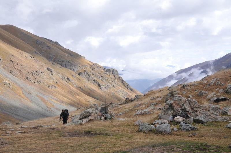 Hiker climbing mountain against cloudy sky