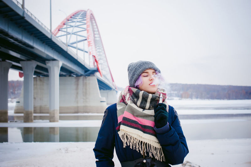 Vaping Architecture Built Structure Cold Temperature Connection Day Front View Knit Hat Leisure Activity Lifestyles Nature One Person Outdoors Real People Scarf Snow Vape Warm Clothing Winter Young Adult Young Women
