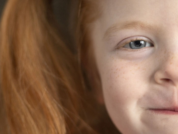 A extreme close-up of a five-year-old girl with red hair and blue eyes. Close-up One Person Portrait Headshot Body Part Child Human Face Childhood Hair Lifestyles Women Eye Focus On Foreground Front View Looking Leisure Activity Human Hair Innocence Teenager Hairstyle Pre-adolescent Child Eyebrow Contemplation Red Hair Blue Eyes