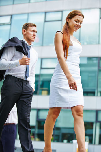 Businessman and businesswoman walking in city