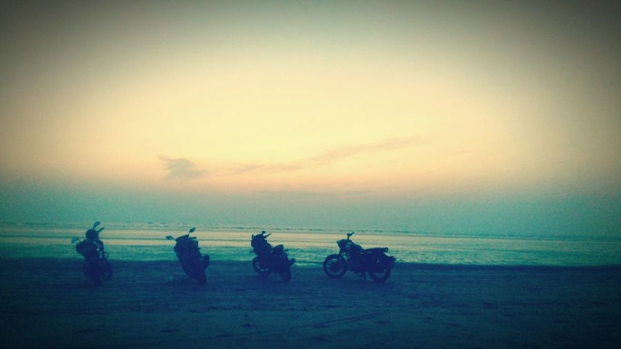 Group of people riding motorcycle at sunset