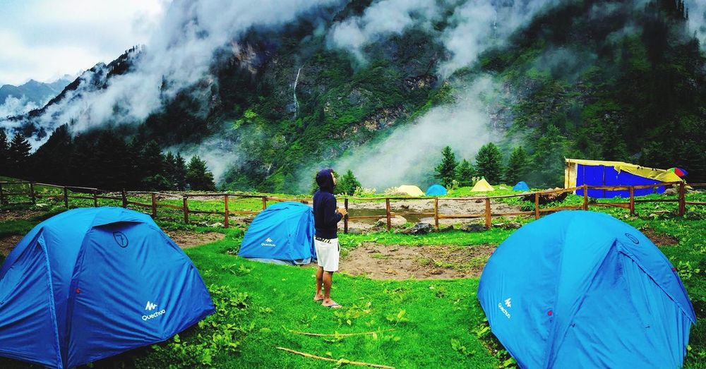 Tent on field against trees and mountains against blue sky