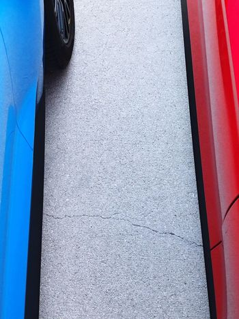 In The Middle Two Cars Red Blue Concrete Driveway Cracked From My Point Of View