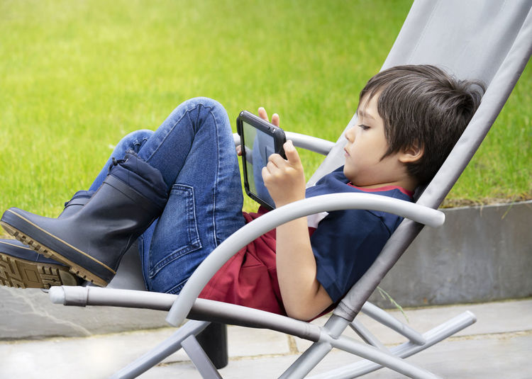 Rear view of boy using mobile phone while sitting on grass