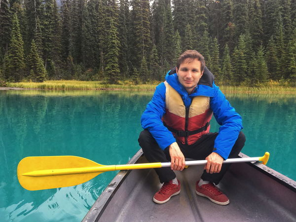 Emerald lake, Canada Canoe Man Activity Adventure Day Forest Front View Full Length Handsome Lake Leisure Activity Lifestyles Looking At Camera Nature Nautical Vessel Oar One Person Outdoors Rowing Sitting Tree Turquoise Water Young Adult