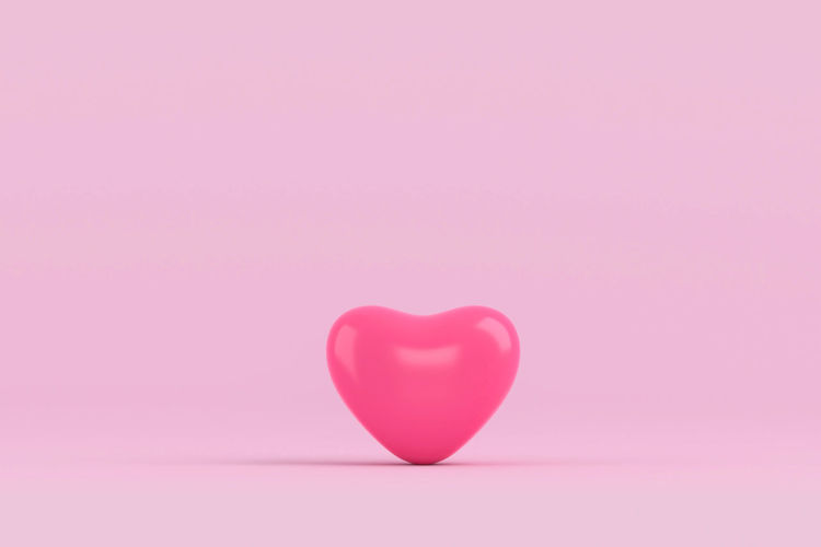 Close-up of heart shape balloon over pink background