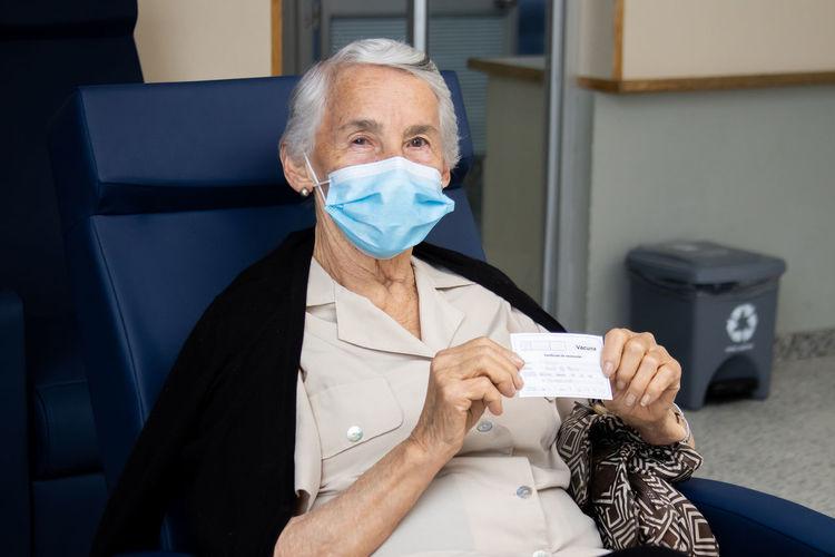 Portrait of senior woman wearing mask holding paper