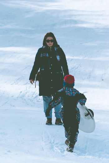 Beautiful woman by son with sled on snow covered field during winter