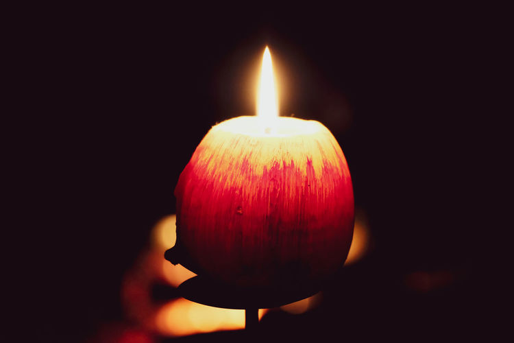 Close-up of lit candle in the dark