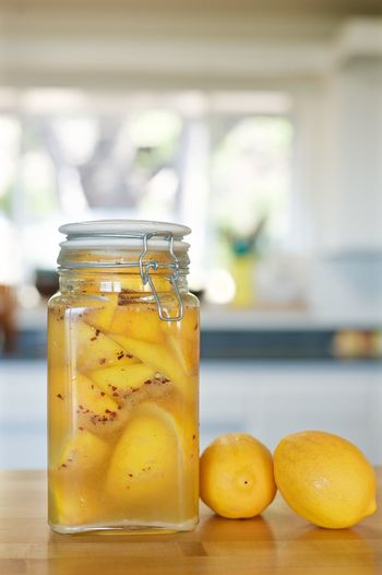 Pickles in glass jar by lemons on table at home