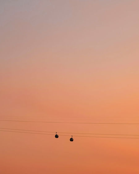 Low angle view of silhouette overhead cable cars against orange sky during sunset