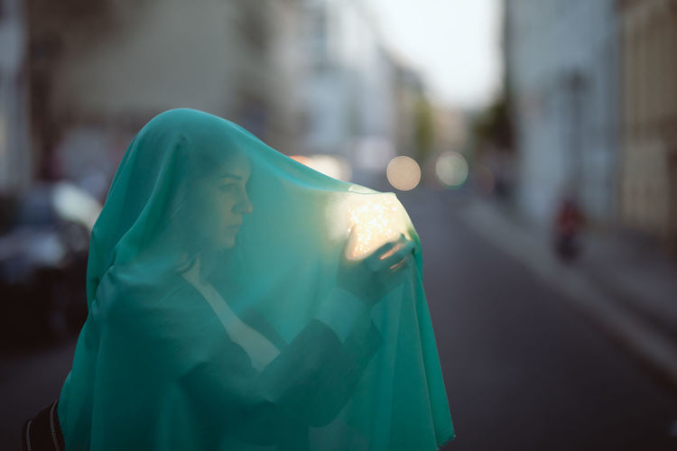 Woman holding glowing jar under blue scarf on city street at dusk