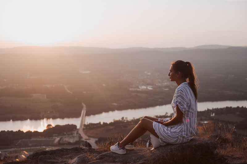 Woman sitting on mountain against sky during sunset