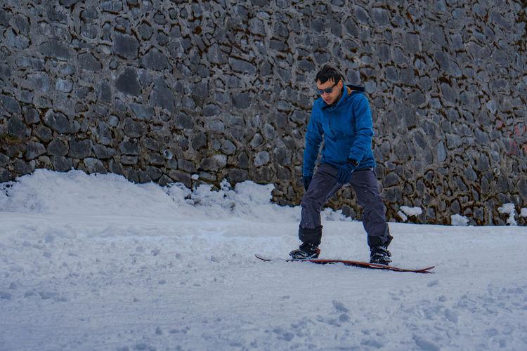 Full length of man snowboarding against wall