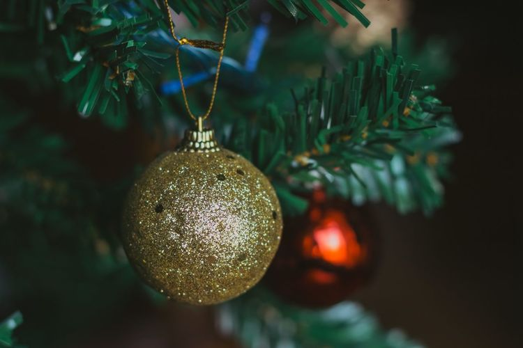 Golden christmas ball. golden glitter. close-up of christmas decoration hanging on tree