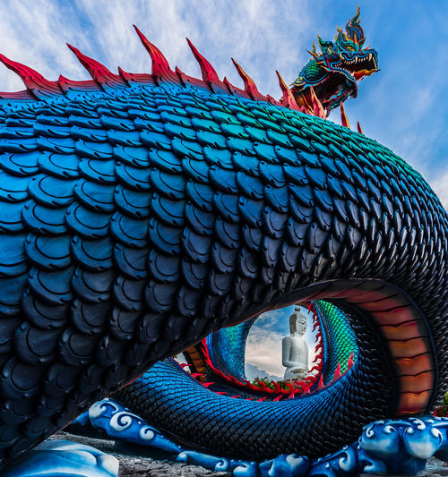 Low angle view of dragon statue against blue sky