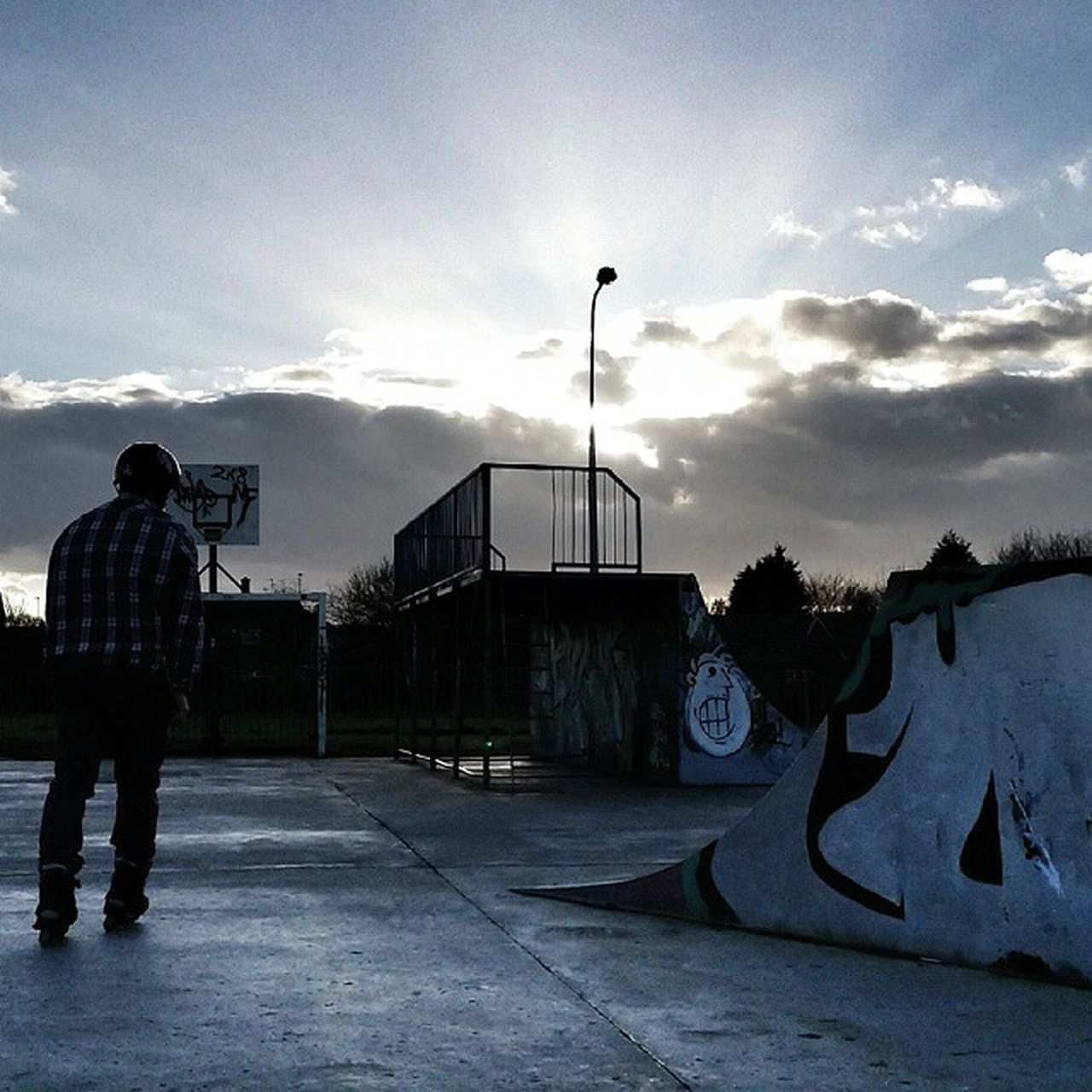 sky, real people, cloud - sky, graffiti, standing, outdoors, rear view, one person, men, built structure, road, day, architecture, full length, skateboard park, people