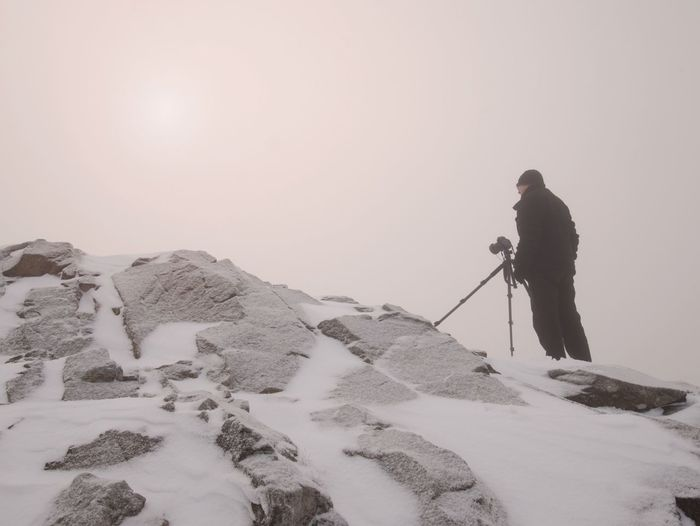 Photographer takes picture of freeze snowy mountains rocks. extreme misty weather. stony rock peak