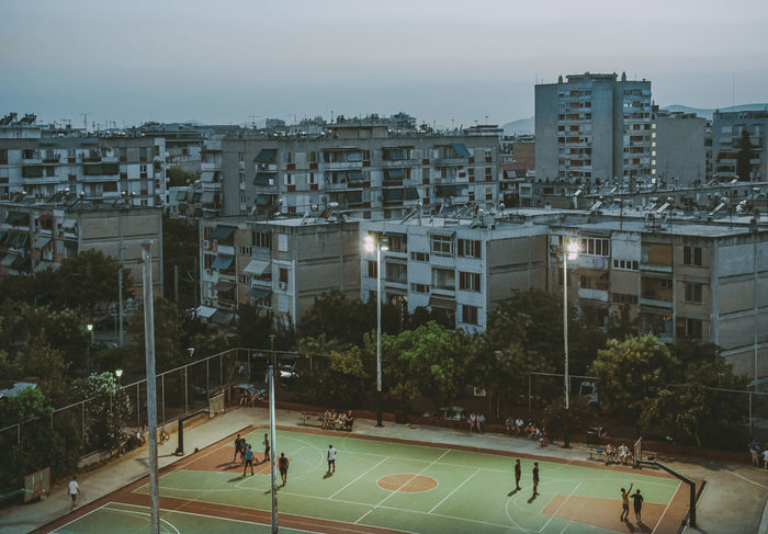 High angle view of people playing soccer on field against buildings