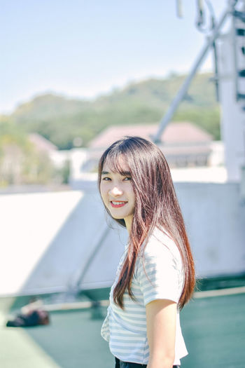 Portrait of young woman smiling while standing against retaining wall