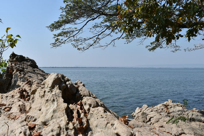 bright sunny blue sky over smooth lake surface Peaceful View Rock Green Trees And Great Rocks In The Lake Horizon Over Water Peaceful Place Photography Photography Lovers Relaxing View Stone Strong Viewpoint