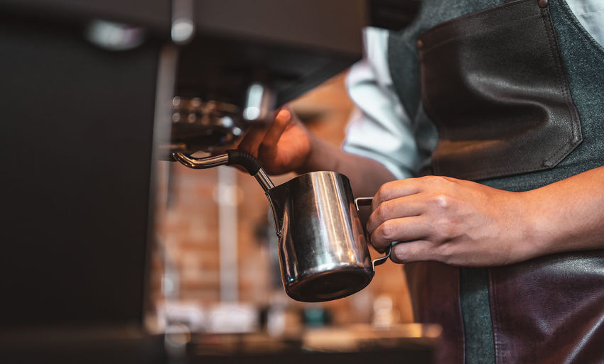 Midsection of barista working in cafe
