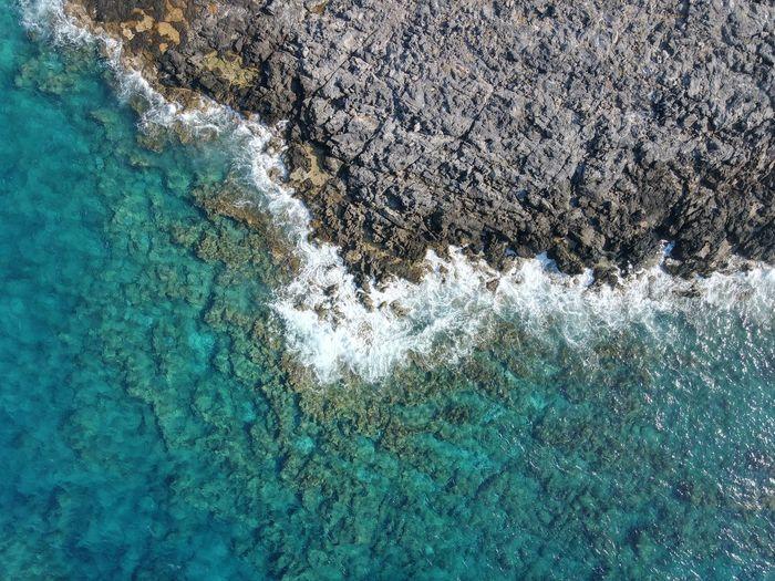 Drone shot of rocky coast line in crete, near chania, stravos beach, greece