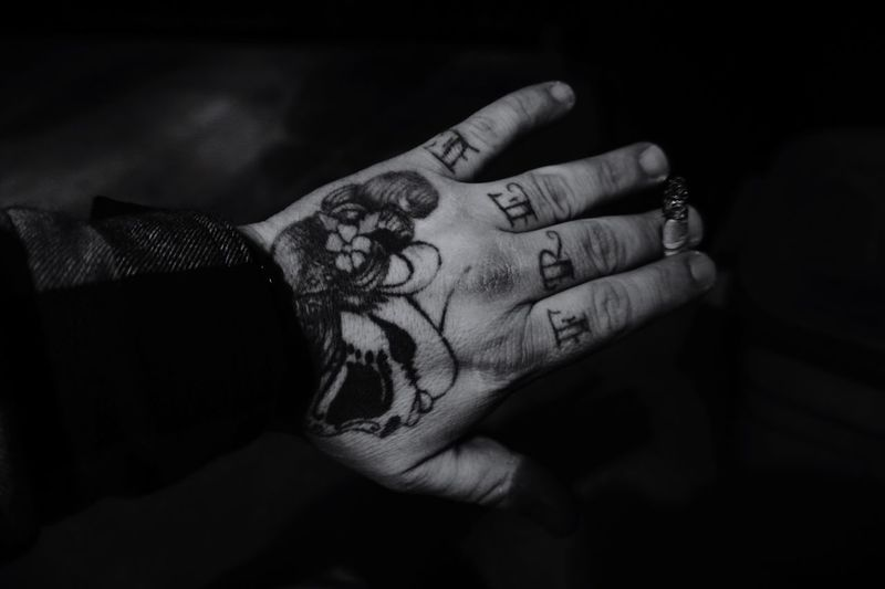 Cropped image of tattooed hand holding burnt cigarette