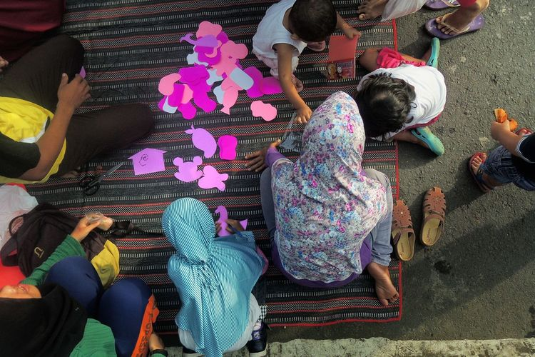 High Angle View Of Children With Craftwork