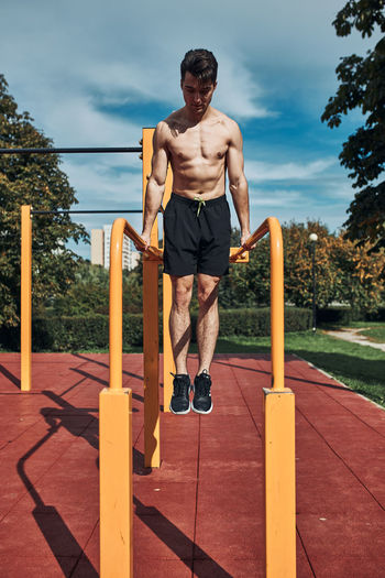 Young shirtless bodybuilder doing dips on parallel bars during his workout in a calisthenics park