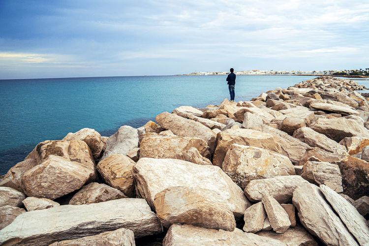 Rocks standing on rock by sea against sky