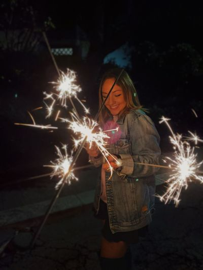 Smiling young woman holding sparklers at night
