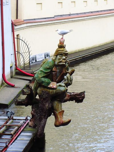 """Grotesque figure by the medieval mill on the """"Devil's Channel"""" Certovka in Prague Praha"""