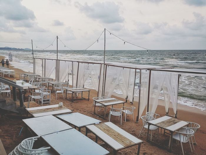 Empty chairs and table on beach against sky