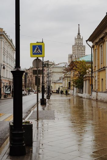 Road sign on wet street against buildings in city