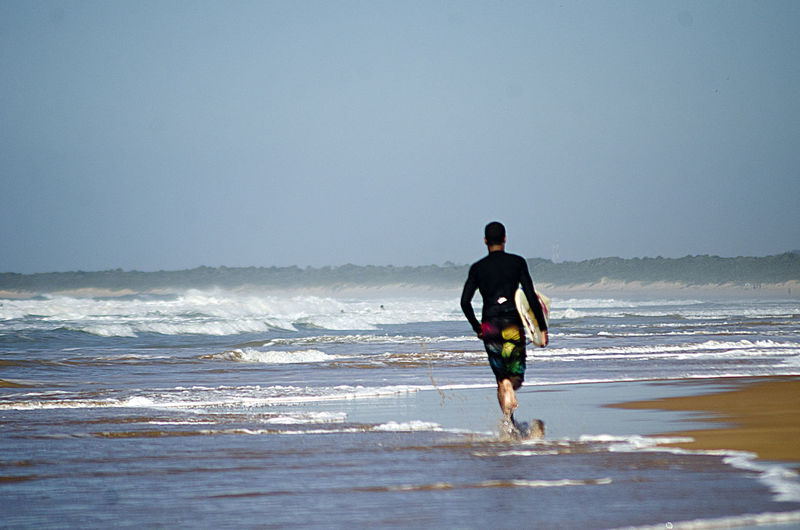 Surfer Running Along Beach