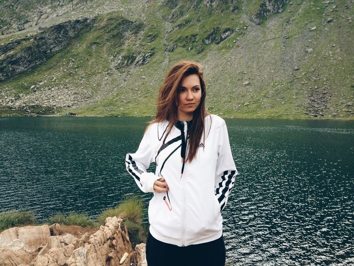 Beautiful Woman Standing At Riverbank Against Mountain