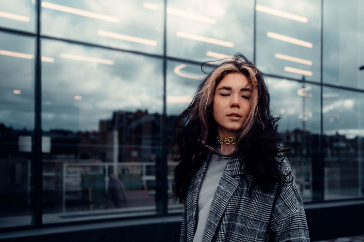 Portrait of beautiful young woman standing against glass wall