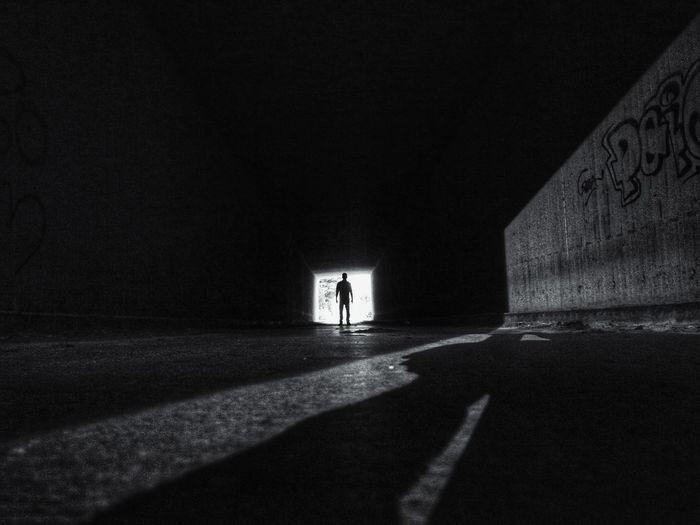 Silhouette people walking on illuminated road