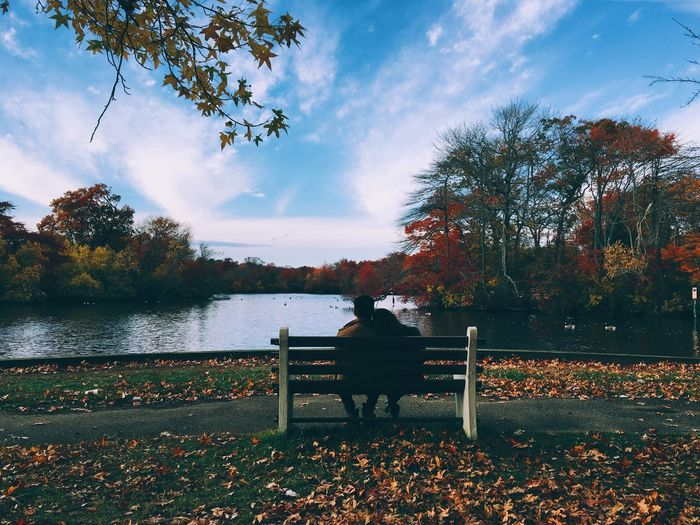 Rear View Of Couple Sitting In Bench By River During Autumn