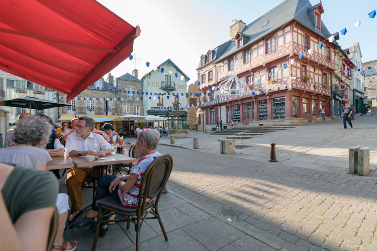People sitting on table by buildings in city