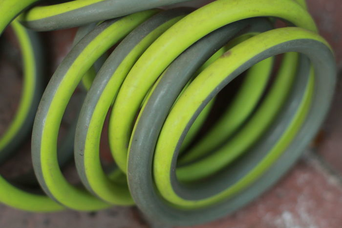 close up of the green coiled garden hose Circling Close-up Day Garden Hose Gardenhose Green Color Hose Nature No People Outdoors Shape Spiral