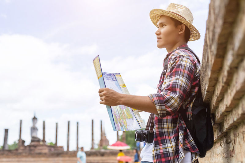 Side view of young woman holding hat against sky
