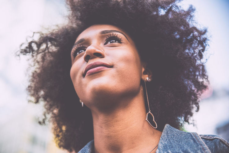 Low Angle View Of Thoughtful Young Woman With Afro Hairstyle In City