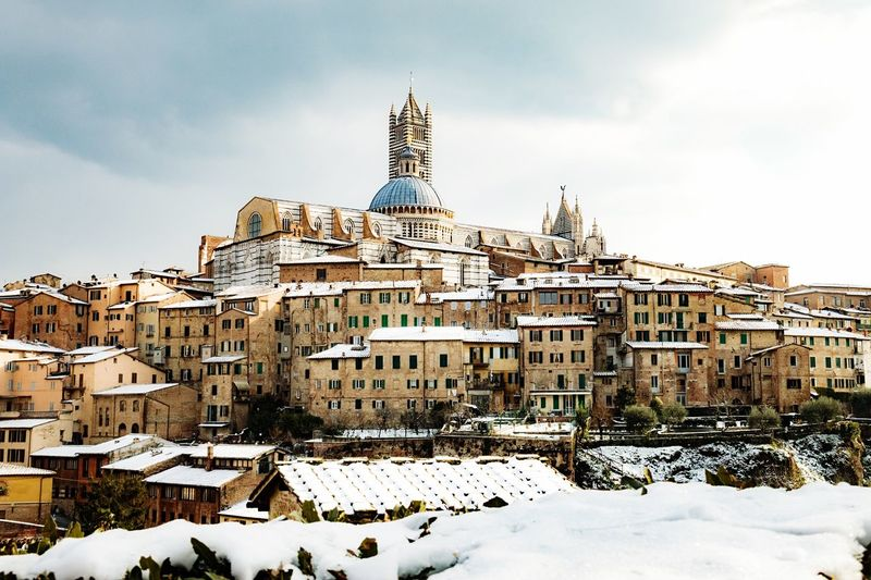 EyeAmNewHere Siena In Snow Old Town Historical Building Religious Architecture Tourism In Italy Tourist Attraction  Cathedral Dome Architecture Built Structure Cold Temperature Winter Building Exterior Snow Sky