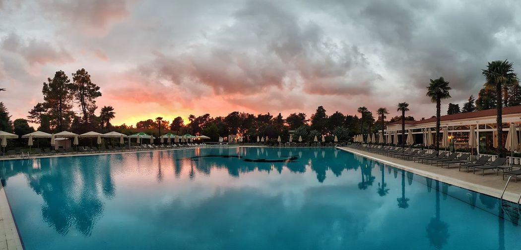 Peace before the storm Batumi Tree Water Swimming Pool Sunset Reflection Multi Colored Sky Cloud - Sky Reflecting Pool Reflection Lake Calm Palm Tree Standing Water Sky Only Atmospheric Mood Dramatic Sky Storm Cloud Idyllic Date Palm Tree Tropical Tree Palm Frond